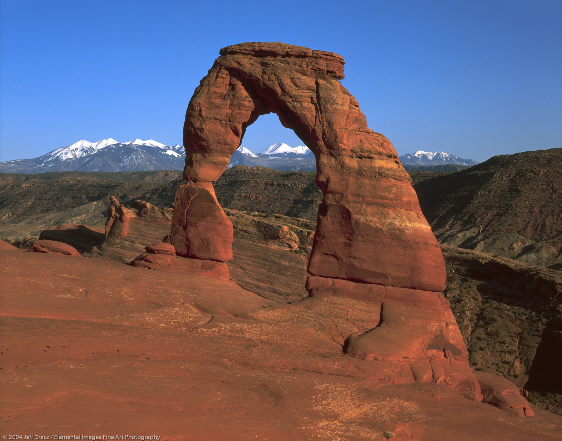 Delicate Arch with distant La Sal Mtns | Arches National Park | UT | USA - © © 2004 Jeff Gracz / Elemental Images Fine Art Photography - All Rights Reserved Worldwide